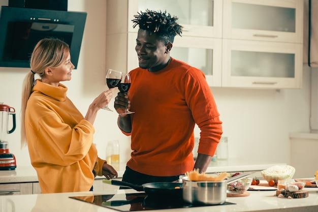 Vrolijke jonge dame lacht naar haar gelukkige vriendje terwijl ze met hem in de keuken staat en geniet van heerlijke rode wijn