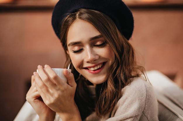 Vrolijke jonge dame met rode lippen, gesloten ogen, bruin haar, stijlvolle baret en beige pullover die buiten zit, glimlacht en een witte kop thee vasthoudt op zonnige herfstdag