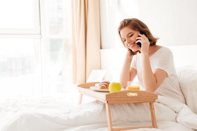 Vrolijke jonge dame zitten binnenshuis met croissant drinken sap