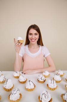Vrolijke jonge dame zitten en poseren in de buurt van cupcakes op tafel