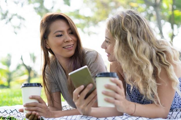 Vrolijke jonge dames die koffie drinken en gadget samen gebruiken