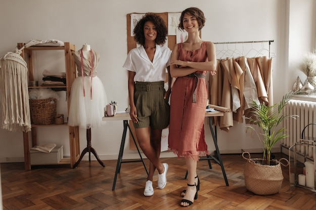 Vrolijke jonge dames in stijlvolle outfits leunen op een bureau in een gezellig kantoor