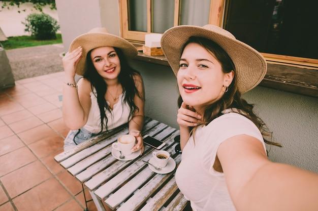 Vrolijke jonge dames nemen koffiepauze aan de tafelbar en maken een selfie-foto