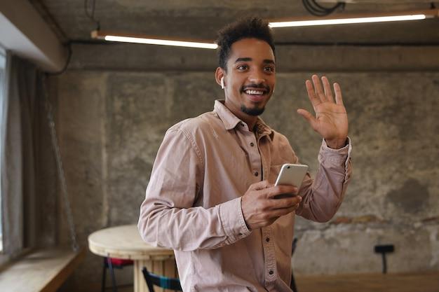 Vrolijke jonge donkere bebaarde bebaarde man in beige overhemd ontmoet bekende persoon en verhogen palm in hallo gebaar, blij om iemand te zien, poseren over coworking space