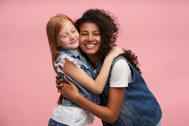 Vrolijke jonge donkere brunette vrouw met lang krullend haar glimlachend gelukkig en knuffelen schattige positieve roodharige vrouwelijke jongen, geïsoleerd op roze