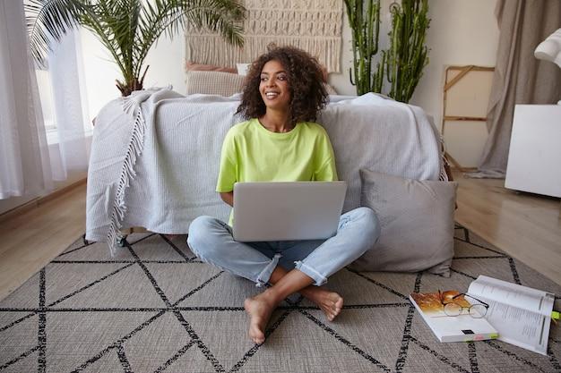Vrolijke jonge donkere vrouw zittend op de vloer in vrijetijdskleding, studeren met texbooks en moderne laptop, vreugdevol glimlachen en in een leuke bui