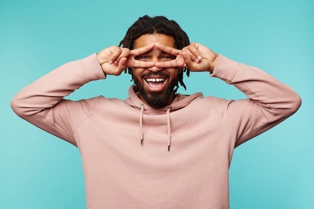 Vrolijke jonge donkerhuidige brunette man met dreadlocks verhogen handen met overwinning gebaar naar zijn gezicht en vrolijk kijken naar camera met brede glimlach, geïsoleerd op blauwe achtergrond