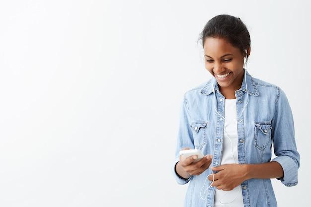 Vrolijke jonge donkerhuidige jonge vrouw in blauw overhemd die gelukkig en opgewekt voelen terwijl het lezen van bericht op slimme telefoon, wat positief nieuws ontvangt.