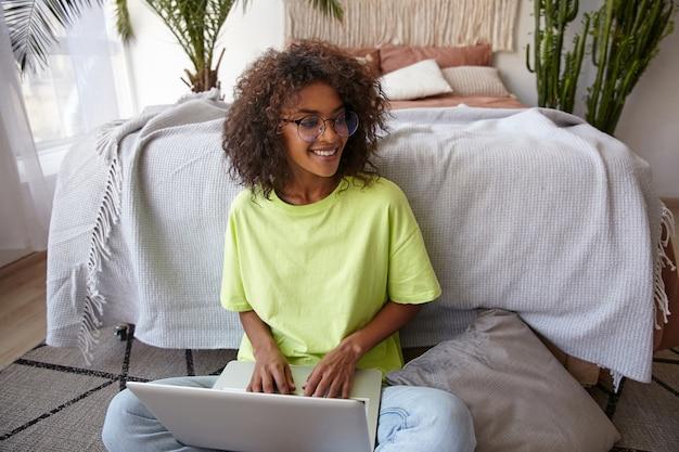 Vrolijke jonge donkerhuidige vrouw met bril leunend op bed in de slaapkamer, werken vanuit huis met laptop, handen houden op het toetsenbord, in een goede bui