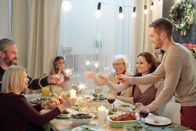 Vrolijke jonge en volwassen volwassenen die fonkelende bengaalse lichten houden over de gediende tafel terwijl het meisje door het raam haar mond bedekt