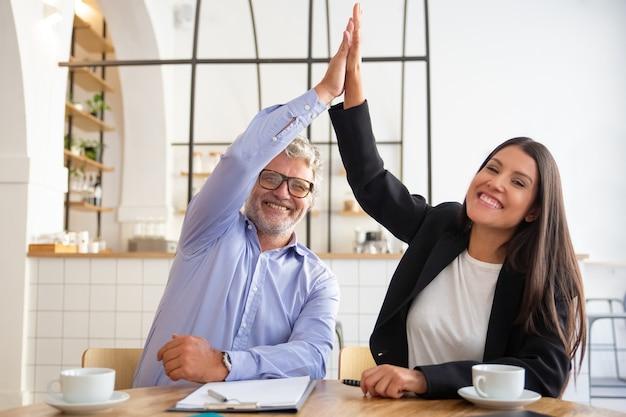 Vrolijke jonge en volwassen zakenpartners geven high five en vieren succes, zittend aan tafel met documenten en koffiekopjes