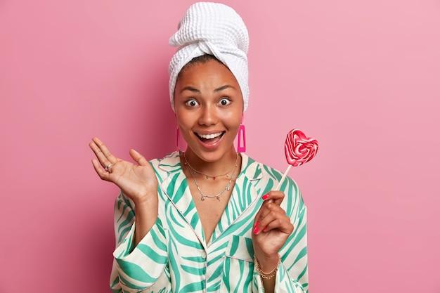 Vrolijke jonge etnische vrouw glimlacht breed, heeft een gezonde huid, geniet van schoonheid en spa-procedures thuis, houdt lolly op stok, draagt ochtendjas, gewikkeld handdoek op hoofd. binnenlandse levensstijl