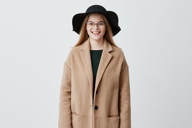 Vrolijke jonge europese vrouw met prachtige functies, gekleed in jas over groene trui, draagt haar blonde haren los, met een bril op, op zoek met charmante glimlach