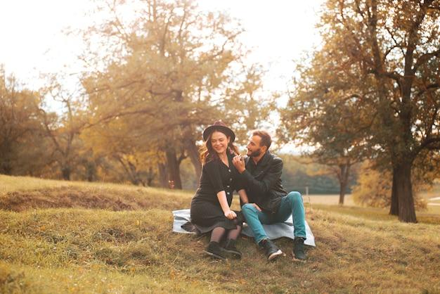 Vrolijke jonge familie met een geweldige tijd in park een zwangere vrouw en haar man