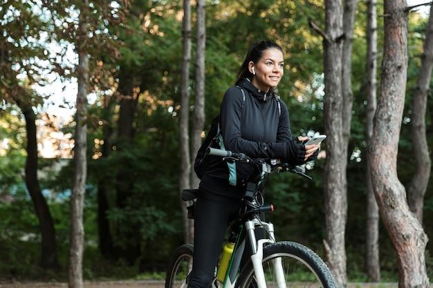 Vrolijke jonge fitness vrouw rijden op een fiets in het park, luisteren naar muziek met koptelefoon, mobiele telefoon houden