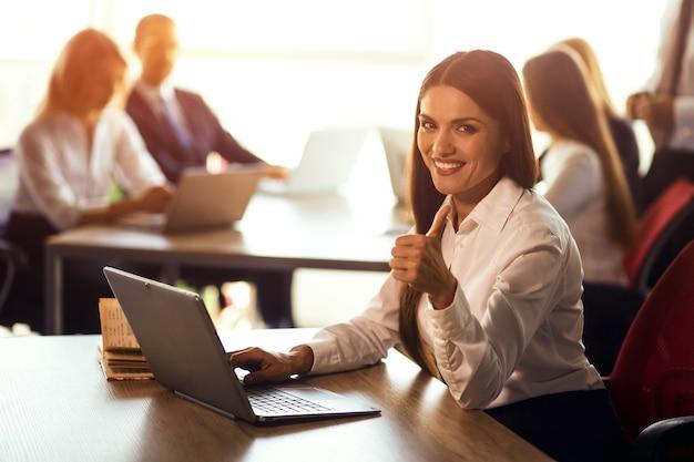 Vrolijke jonge freelance vrouw die op laptop werkt, zittend op het open ruimte kantoor of coworking. werkende vrouw die werkt aan een zakelijk voorstel of it-toepassingen ontwikkelt. afgezwakt beeld.