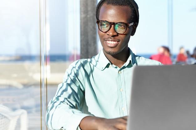 Vrolijke jonge freelancer in een trendy hoed en brillen die gelukkig glimlachen