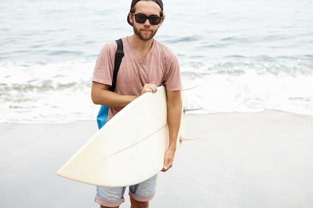 Vrolijke jonge gebaarde toerist in zonnebril die bodyboard houden en met tevreden glimlach kijken, gelukkig met zijn eerste brandingsrit tijdens vakantie in tropisch land