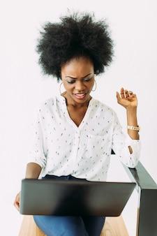 Vrolijke jonge geconcentreerd en verwarde afro amerikaanse bedrijfsvrouw, gebruikend laptop, geïsoleerd op wit