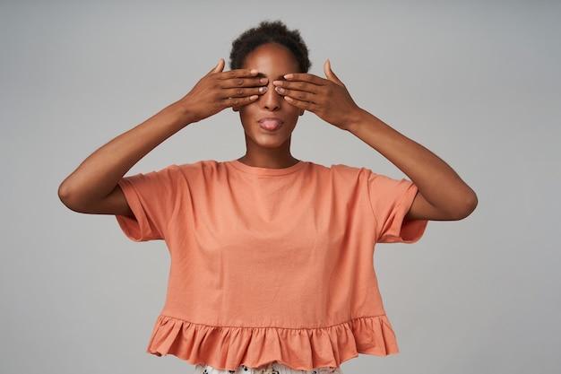 Vrolijke jonge gekrulde brunettened vrouw met casual kapsel die de handpalmen op haar ogen houdt terwijl ze graag haar tong laat zien, geïsoleerd over grijze muur