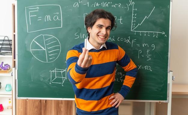 Vrolijke jonge geometrieleraar die voor het bord in de klas staat en de hand op de taille houdt en naar de voorkant kijkt en het krijt naar voren uitstrekt