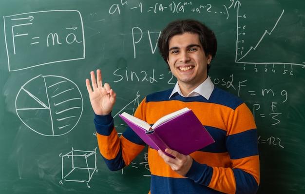 Vrolijke jonge geometrieleraar die voor het bord in de klas staat met een boek dat naar de voorkant kijkt en een goed teken doet