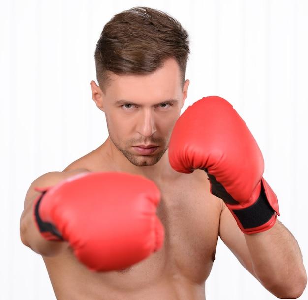 Vrolijke jonge gespierde man bokser training in bokshandschoenen