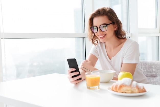 Vrolijke jonge geweldige vrouw chatten via de mobiele telefoon.