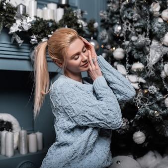 Vrolijke jonge glamoureuze blonde vrouw in een modieuze gebreide trui is ontspannen in een gezellige woonkamer in de buurt van een kerstboom en een vintage open haard
