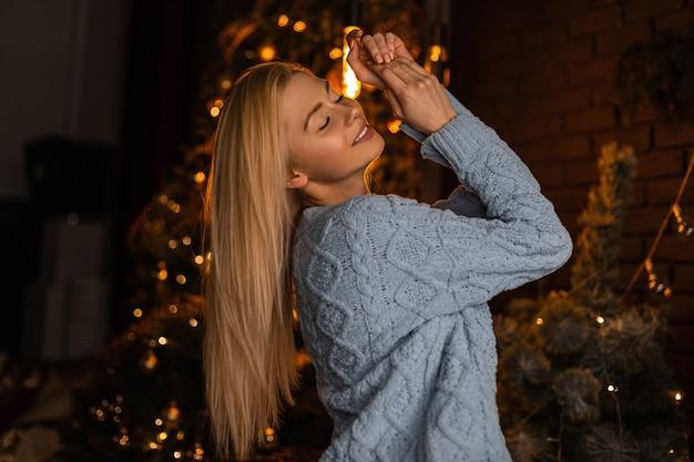 Vrolijke jonge glamoureuze blonde vrouw in een modieuze gebreide trui ontspant in een donkere woonkamer op de achtergrond van een kerstboom met prachtige lichten