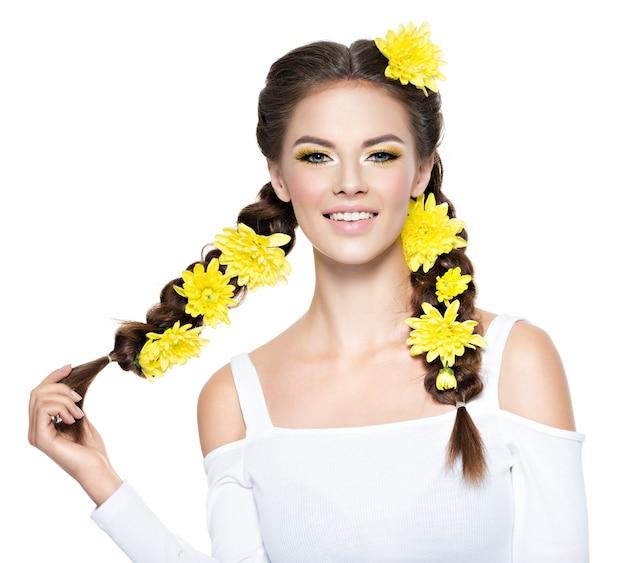Vrolijke jonge glimlachende mooie vrouw met lange vlechten. mode portret. aantrekkelijk meisje met heldere gele make-up - geïsoleerd op wit. professionele make-up. kunst kapsel.