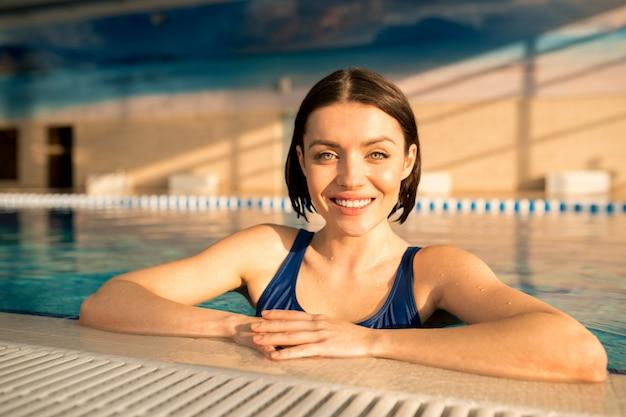 Vrolijke jonge glimlachende vrouw met nat donker haar die zich in water bevinden terwijl het genieten van van vrije tijd in zwembad