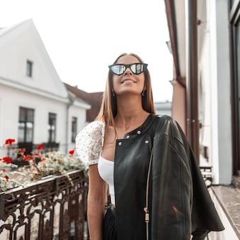 Vrolijke jonge hipster vrouw met een positieve glimlach in modieuze zonnebril in een zwarte jas geniet van ontspanning staande op een vintage balkon in een zonnige herfstdag. blij meisje buitenshuis rusten.
