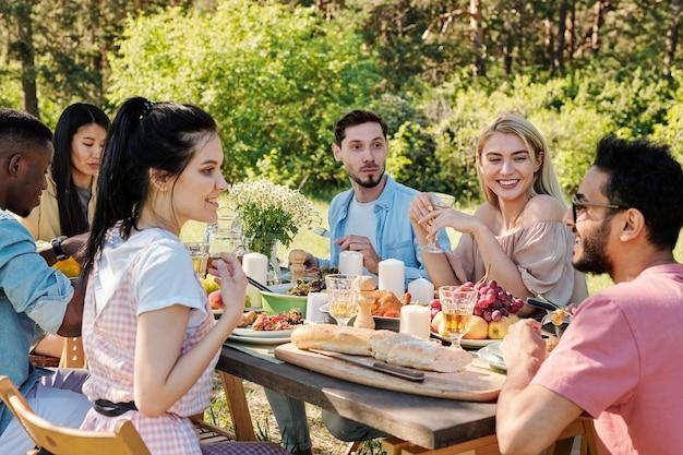 Vrolijke jonge interculturele mannen en vrouwen in vrijetijdskleding praten zittend aan tafel geserveerd met zelfgemaakte gerechten en vers fruit