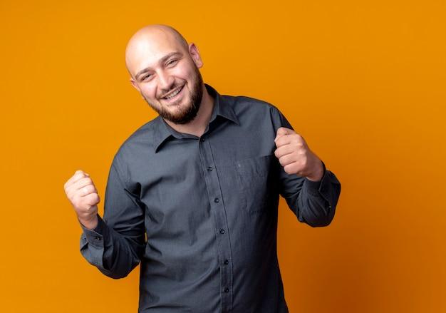 Vrolijke jonge kale call center man balde vuisten geïsoleerd op oranje
