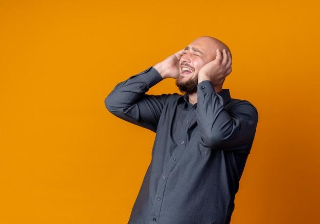 Vrolijke jonge kale call center man handen op het hoofd zetten met gesloten ogen geïsoleerd op oranje
