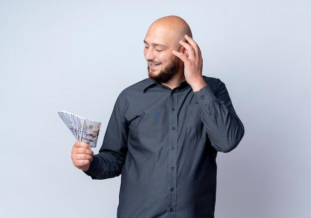 Vrolijke jonge kale call center man houden en kijken naar geld met hand op hoofd geïsoleerd op wit