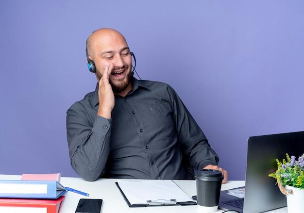 Vrolijke jonge kale callcentermens die hoofdtelefoon draagt die aan bureau zit met uitrustingsstukken die laptop bekijkt en hand dichtbij mond zet die op paars wordt geïsoleerd