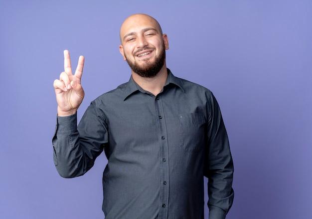 Vrolijke jonge kale callcentermens die vredesteken doet dat op paars wordt geïsoleerd