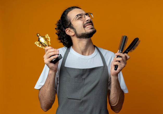 Vrolijke jonge kaukasische mannelijke kapper bril en golvende haarband dragen uniform houden kammen en winnaar beker met gesloten ogen geïsoleerd op een oranje achtergrond