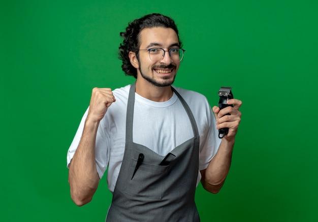 Vrolijke jonge kaukasische mannelijke kapper bril en golvende haarband in uniform bedrijf tondeuse en balde vuist geïsoleerd op groene achtergrond met kopie ruimte