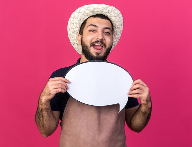 Vrolijke jonge kaukasische mannelijke tuinman die tuinieren hoed draagt die toespraakballon houdt die op roze muur met exemplaarruimte wordt geïsoleerd