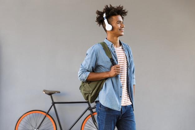 Vrolijke jonge kerel die buiten loopt met de rugzak van de fiets het luisteren muziekholding