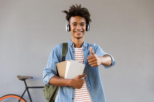 Vrolijke jonge kerel die buiten met boeken loopt die van de fiets het luisteren muziek houden duimen opdagen