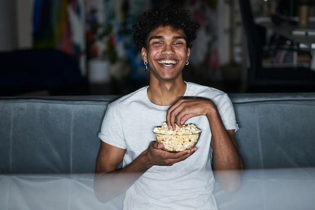 Vrolijke jonge kerel in pyjama die wat popcorn uit een kom neemt terwijl hij naar komedie kijkt terwijl hij op een