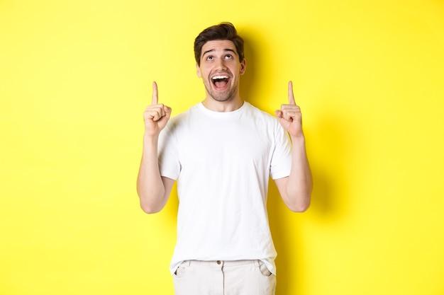 Vrolijke jonge kerel in wit t-shirt die op promo-aanbieding reageert, met verbazing wijst en omhoog kijkt, zich over gele achtergrond bevindt.