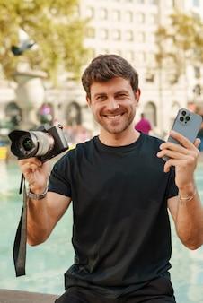 Vrolijke jonge kerel zit in de buurt van fontein met moderne fotocamera en smartphone