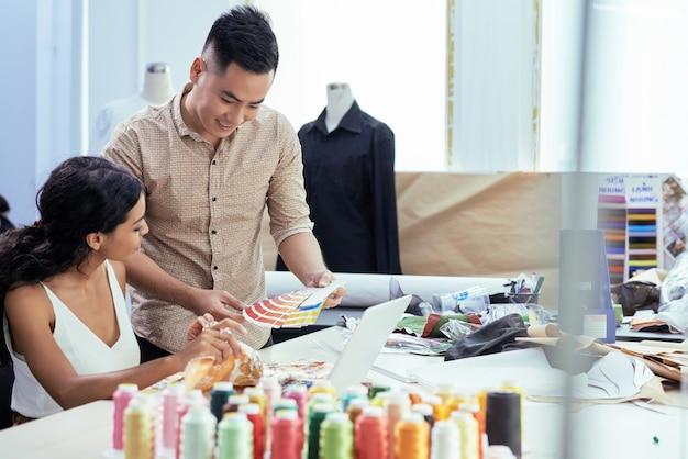 Vrolijke jonge kleermakers bespreken palet van monsters bij het kiezen van stof voor nieuwe collectie