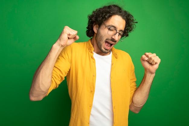 Vrolijke jonge knappe blanke man met bril doet ja gebaar met gesloten ogen geïsoleerd op groene achtergrond