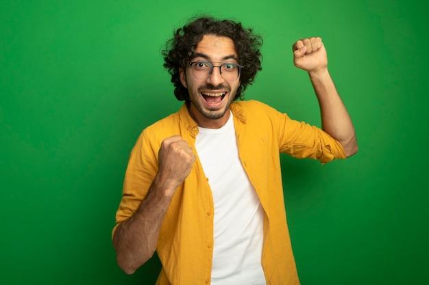 Vrolijke jonge knappe blanke man met bril kijken camera doen ja gebaar geïsoleerd op groene achtergrond met kopie ruimte